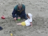 Grandpa buries CareBear in the sand.